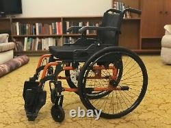 Black and orange frame Care Co wheelchair. Lightweight and foldable. Good design